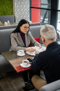 Selective focus of asian businesswoman talking with businessman and holding papers in cafe stock vector