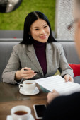 selective focus of smiling asian businesswoman talking with businessman and holding papers in cafe