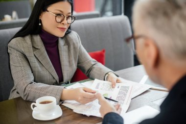 Selective focus of smiling asian businesswoman talking with businessman and pointing at papers in cafe stock vector