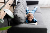 selective focus of cute kid using digital tablet while lying on sofa