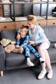 dítě dotýkající se dýchací masky na medvídka poblíž matky sedící na pohovce