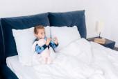 nemocné dítě pomocí inhalátoru s rozpěrkou v blízkosti králičí hračky