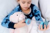 szelektív fókusz beteg gyerek holding inhalátor távtartóval közel nyuszi játék