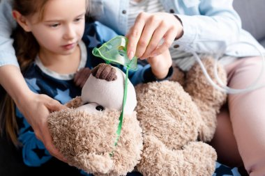 Selective focus of mother touching respiratory mask on teddy bear near sick kid stock vector
