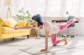 Woman with colorful hair doing asana with outstretched hand and raised leg on yoga mat in living room