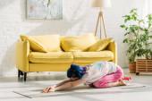 Fotografie Mädchen mit bunten Haaren in Kinderpose auf Yogamatte im Wohnzimmer