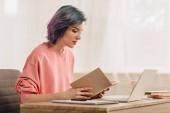 Szabadúszó színes haj olvasókönyv közelében laptop asztal a nappaliban