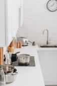 Selektivní zaměření pánví a cezve na povrchu v kuchyni