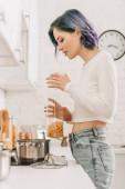 Selektivní zaměření dívky s barevnými vlasy drží kontejner s těstovinami v blízkosti kuchyňského sporáku