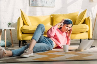 Freelancer with colorful hair and headphones looking at laptop and lying near sofa and cup of tea in living room