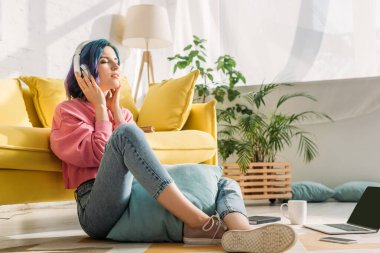Freelancer in headphones with colorful hair and closed eyes near sofa on floor in living room