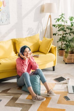 High angle view of freelancer with colorful hair in headphones smiling near sofa on floor in living room