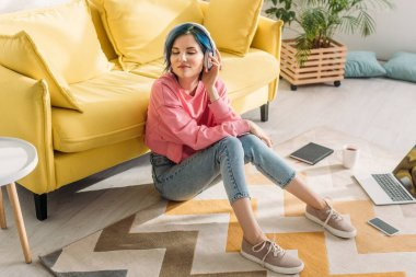 High angle view of freelancer with colorful hair, closed eyes and headphones smiling near sofa on floor