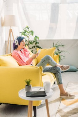 Woman with colorful hair and headphones holding smartphone on sofa near coffee table in living room