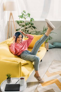 Woman with colorful hair having fun with headphones and raised leg on sofa in living room