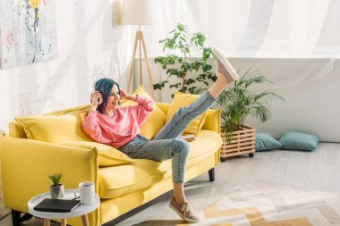 Woman with colorful hair, headphones and raised leg smiling on sofa in living room