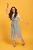 surprised spring woman dancing in elegant dress on yellow