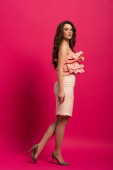 gyönyörű lány áll elegáns ruha rózsaszín