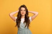 usmívající se jarní dívka s dlouhými vlasy na žluté