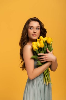 beautiful smiling woman in spring dress holding bouquet of tulip flowers isolated on yellow