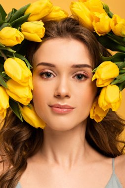 Beautiful smiling girl in fresh tulip flowers isolated on yellow stock vector