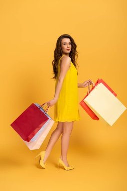 Attractive girl in spring dress holding shopping bags on yellow stock vector