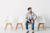 Hezký zaměstnanec odvrací pohled, zatímco sedí na židli v kanceláři