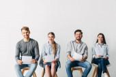 Usmívající se kandidáti s životopisem při pohledu do kamery v kanceláři