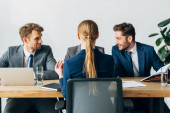 Selective focus of employee sitting at table near smiling recruiters in office