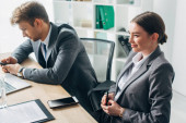 Selective focus of smiling recruiter sitting at table near colleague in office