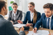 Selective focus of recruiter talking to employee with resume near colleagues at table