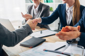 Cropped view of employee shaking hands with recruiter near colleagues during job interview