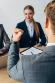 Selective focus of employee showing yes gesture during job interview in office