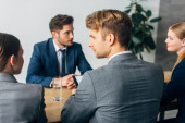 Selective focus of recruiters looking at each other during job interview with employee
