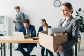 Dismissed woman holding cardboard box near colleagues working in office