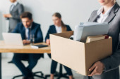 Selective focus of fired woman holding cardboard box with book and papers in office