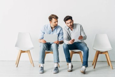 Candidates with laptop looking at resume while waiting for job interview in office