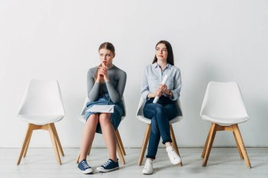 Thoughtful candidates with resume waiting for job interview in office