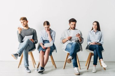 Group of young people with resume waiting for job interview in office