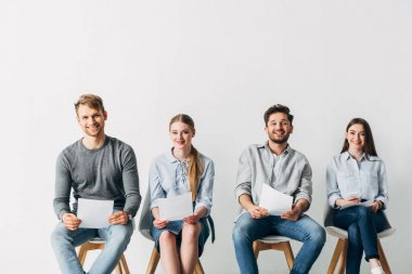 Smiling candidates with resume looking at camera in office