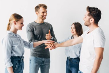 Smiling man showing thumb up while holding hands with coworkers in office