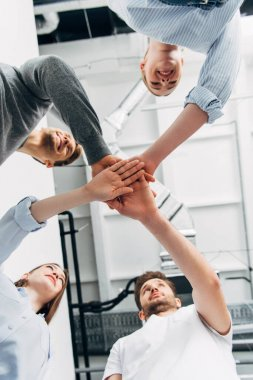 Bottom view of smiling colleagues holding hands in office