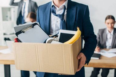 Selective focus of dismissed man holding cardboard box with papers, digital tablet and banana in office stock vector