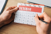 Cropped view of man holding pen and calendar with october month near laptop on table