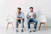 Selbstbewusster Mitarbeiter mit Laptop sitzt neben Mann mit Lebenslauf im Büro
