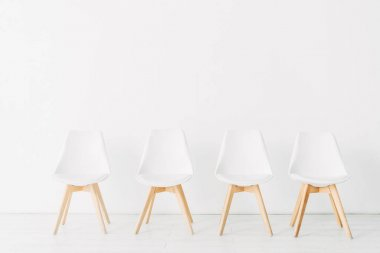 Row of chairs near white wall in office stock vector