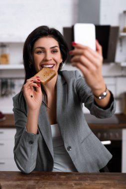 Selective focus of smiling woman with black dot on palm eating tasty toast bread and taking selfie, domestic violence concept stock vector