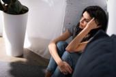 Fényképek szelektív fókusz a szomorú nő zúzódások arcán ül a padlón otthon, családon belüli erőszak koncepció