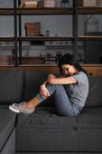 Fényképek depressziós nő zúzódásokkal az arcán ül a kanapén a nappaliban, családon belüli erőszak fogalma