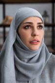 Verärgerte muslimische Frau im Hidschab schaut auf, Konzept häuslicher Gewalt